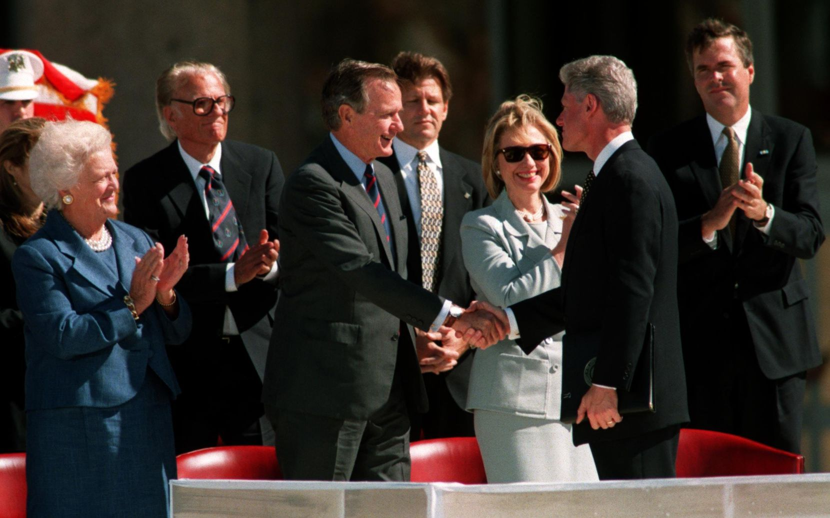 Former President George H.W. Bush and then-President  Bill Clinton shook hands at the  dedication ceremony for the George Bush Presidential Library and  Museum at Texas A&M University. Also attending, from left, were Barbara Bush, the Rev. Billy Graham, Hillary Clinton and Jeb Bush. (1997 File Photo/Staff)
