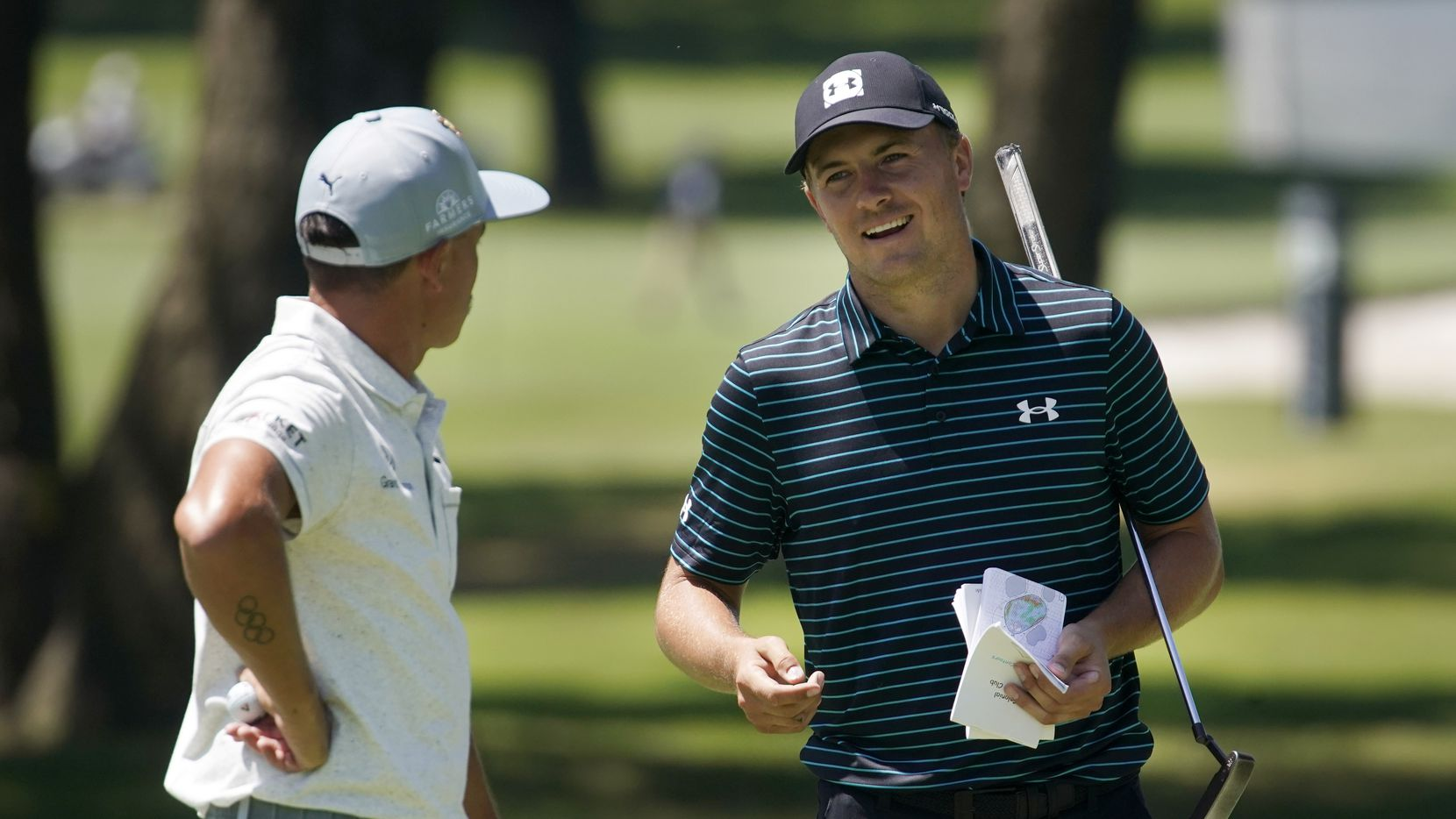 PGA Tour golfer Jordan Spieth visits with playing partner Rickie Fowler after putting on No. 7 during the second round of the Charles Schwab Challenge at the Colonial Country Club in Fort Worth, Friday, June 12, 2020.