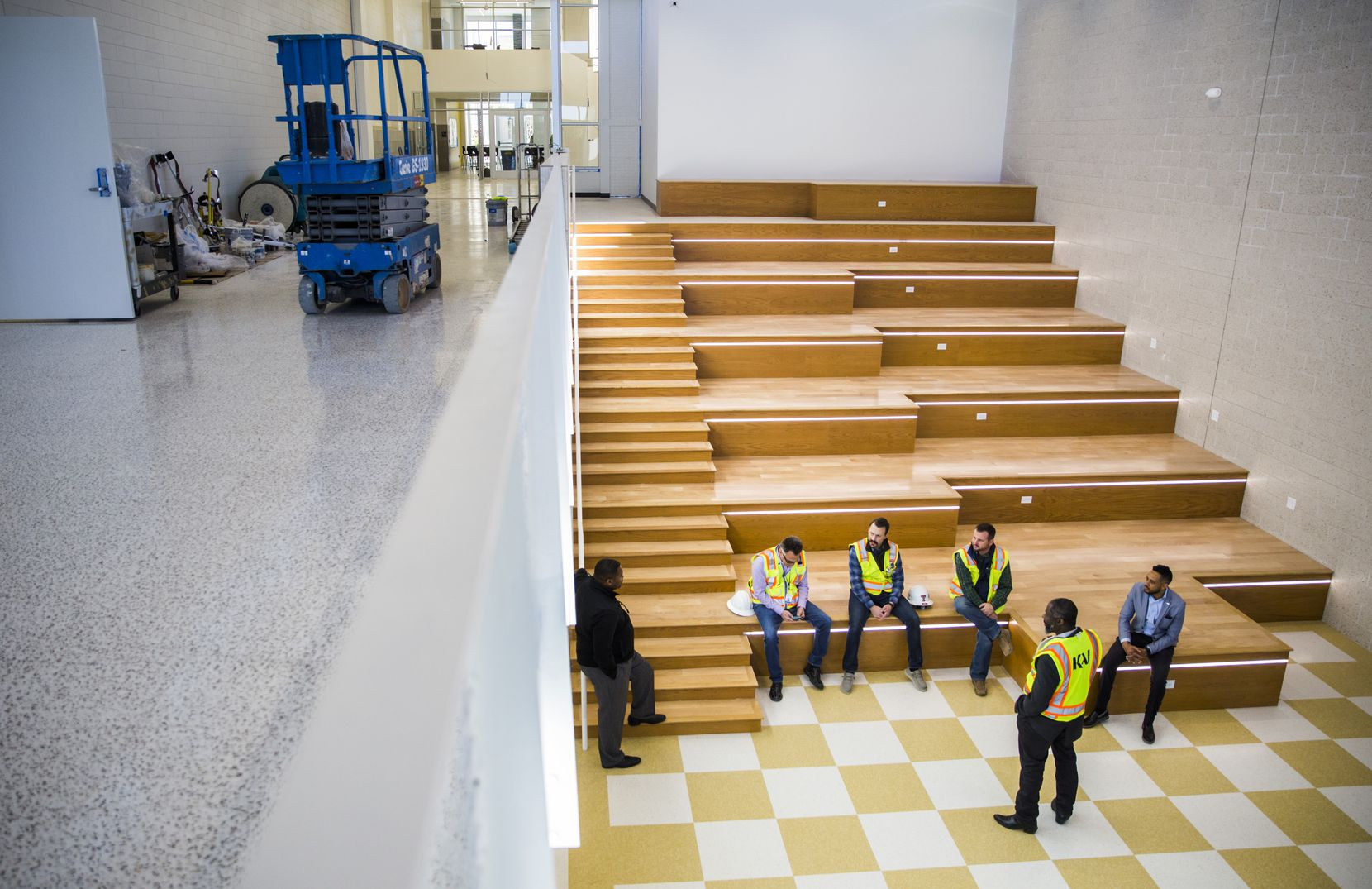 Workers chat in a main hallway and seating area on Thursday, December 19, 2019 at South Oak Cliff High School in Dallas. Workers are finishing a two-year, $52 million renovation to the campus. (Ashley Landis/The Dallas Morning News)