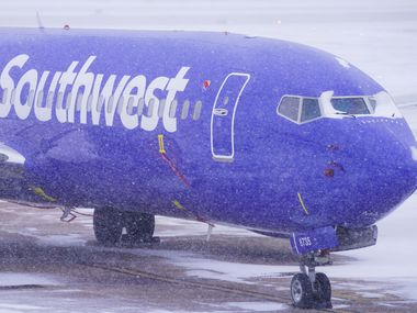 A Southwest Airlines plane sits idle in a parking area at Dallas Love Field as a winter storm brings snow and freezing temperatures to North Texas on Sunday, Feb. 14, 2021, in Dallas. Southwest canceled nearly all its flights out of Love Field.