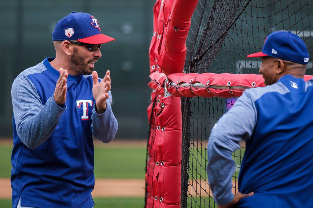 Texas Rangers manager Chris Woodward talks with third base coach Tony Beasley around the batting cage following the first pitchers and catchers spring training workout at the team's training facility on Wednesday, Feb. 13, 2019, in Surprise, Ariz.. (Smiley N. Pool/The Dallas Morning News)