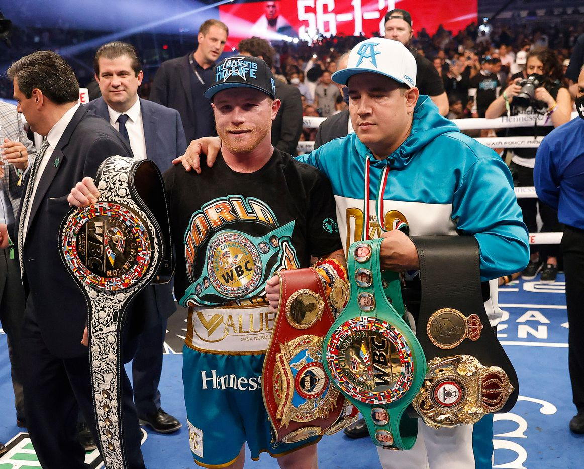 Boxers Canelo Alvarez (left) celebrates with his new WBC belt after defeating Billy Joe Saunders in their unified super middleweight title fight at AT&T Stadium in Arlington, Saturday, May 8, 2021. Saunders couldn't go onto the ninth round because he couldn't see due to an eye injury. (Tom Fox/The Dallas Morning News)