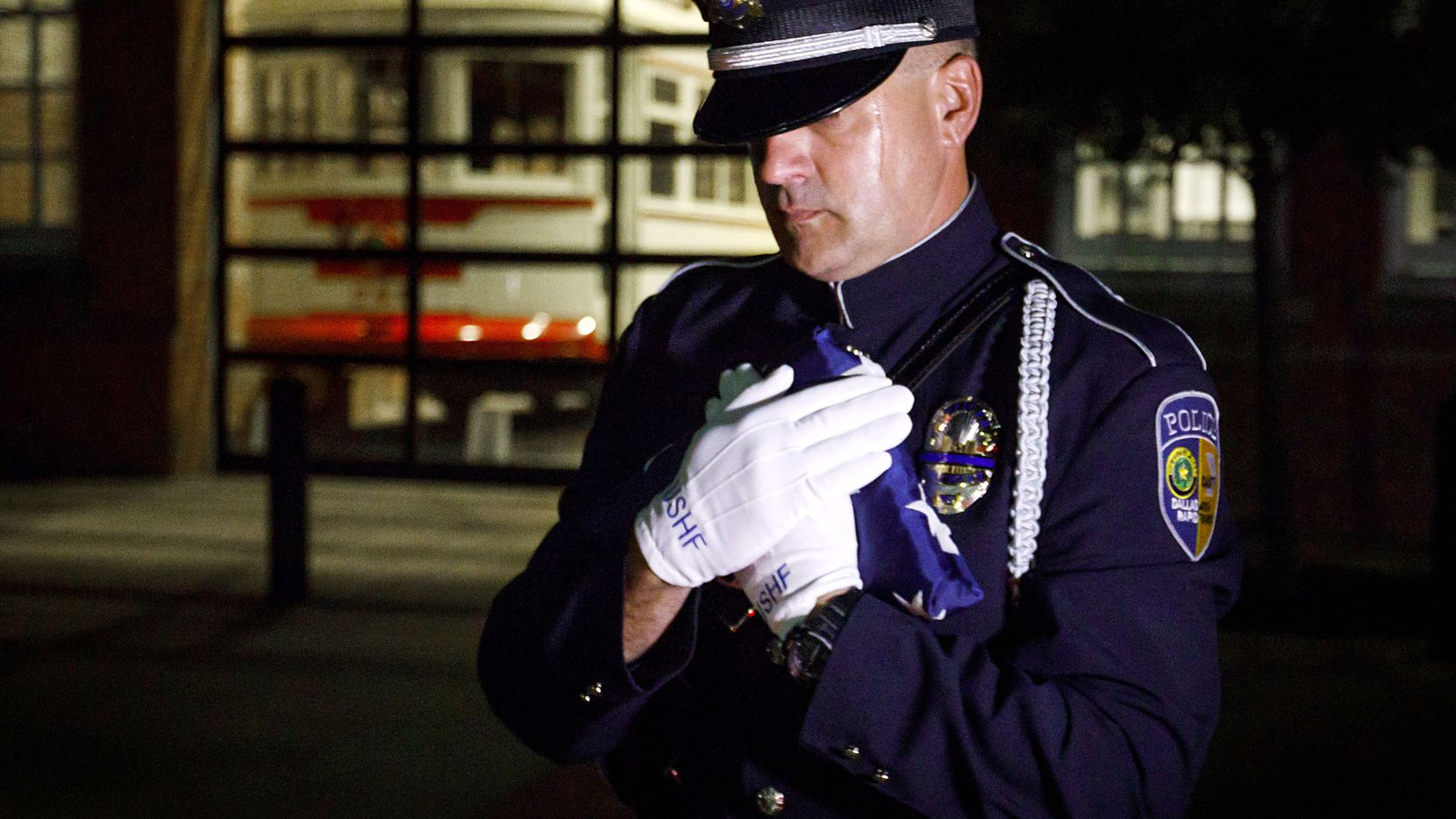 DART Police officer Chris Cobb carries the US Honor Flag as the flag arrives at DART Police headquarters after being transferred from Dallas Police headquarters in the early morning hours of Tuesday, July 11, 2017, in Dallas.