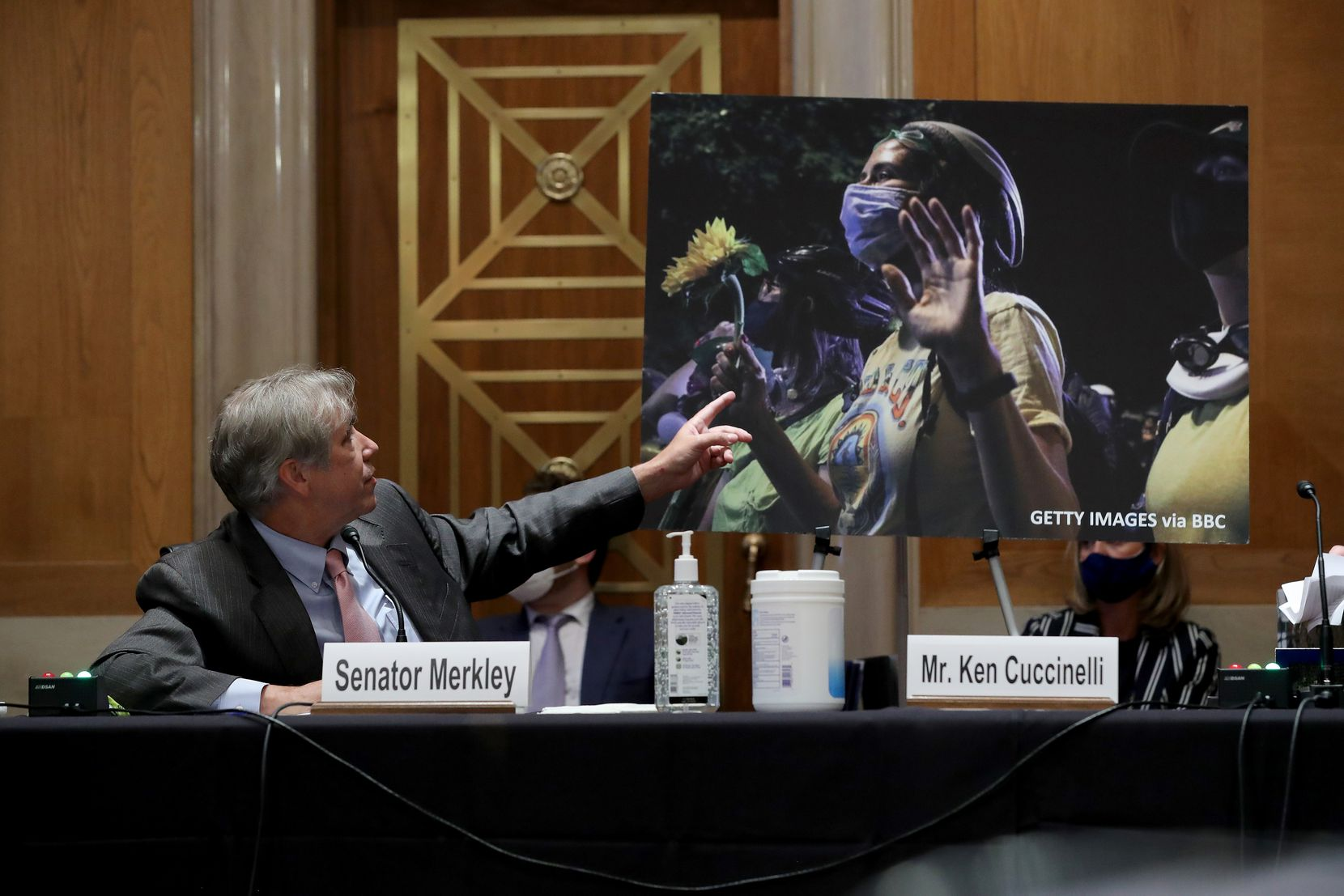 """Sen. Jeff Merkley (D-OR) refers to a photo of peaceful protesters during a Senate Judiciary subcommittee on the Constitution hearing on """"anarchist violence"""" on Aug. 4, 2020, chaired by Sen. Ted Cruz."""