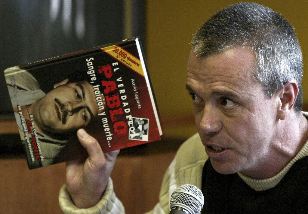 """ARCHIVO - En esta foto de archivo del 27 de junio de 2006, Jhon Jairo Velásquez, un antiguo sicario de Pablo Escobar, conocido por su alias """"Popeye"""", da su testimonio mientras sostiene un libro durante un juicio en Bogotá, Colombia. (AP Foto/William Fernando Martinez, Archivo)"""