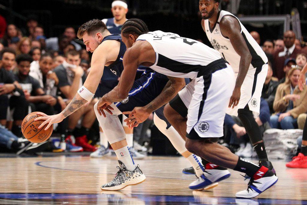 El delantero de los Mavericks de Dallas, Luka Doncic (atrás), controla el balón ante la presión del jugador de los Clippers de Los Ángeles, Kawhi Leonard, el 21 de enero de 2020 en el American Airlines de Dallas.