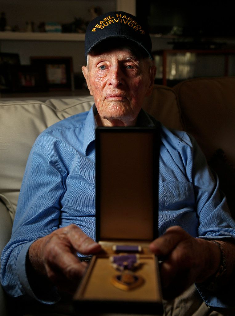 Pearl Harbor survivor John E. Lowe displays his Purple Heart at his son's house in Arlington. Lowe, 96, splits time between his son Dwight's home in Milford and his son John A. Lowe's home in Arlington. (Jae S. Lee/Staff Photographer)