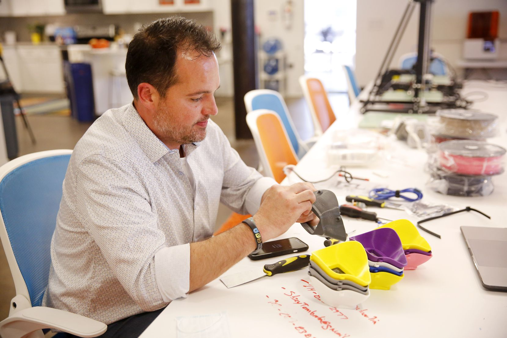 CEO Matt O'Brien sands down a 3-D printed, reusable respiratory mask at Unique Software Development on N. Central Expressway in Dallas, Friday, March 27, 2020.