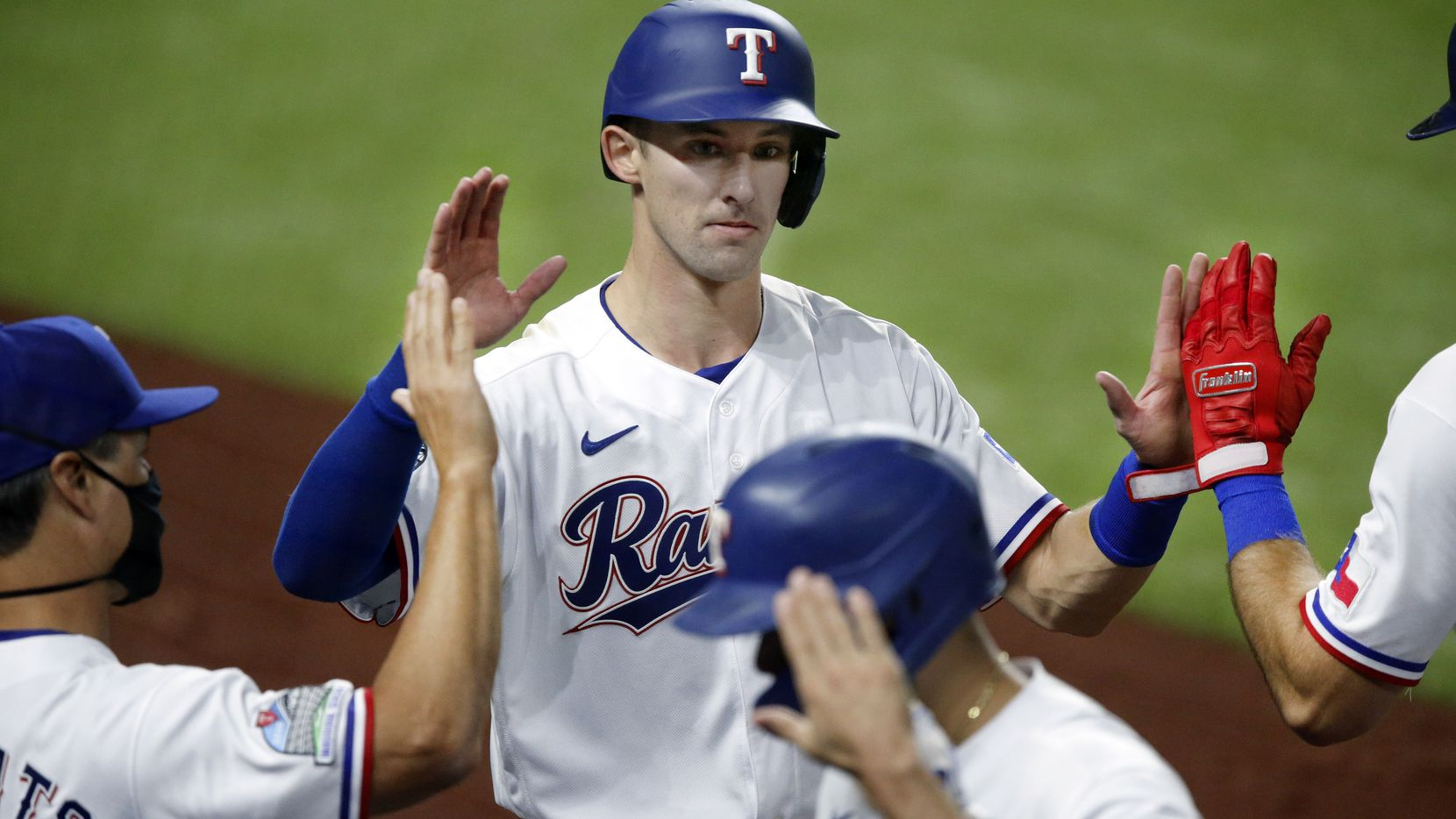 Texas Rangers left fielder Eli White (76) is congratulated by his teammates and coaches after scoring on a sacrifice fly during the fifth inning against the Los Angeles Angels at Globe Life Field in Arlington, Texas, Tuesday, September 8, 2020. White has yet to get his first base hit, despite walking, scoring and getting an RBI. (Tom Fox/The Dallas Morning News)