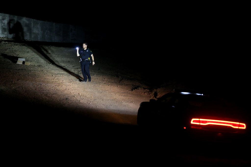 A Dallas police officer searches an area where Weltzin Garcia Mireles and Alfonso Hernandez might have gone missing at White Rock Lake.