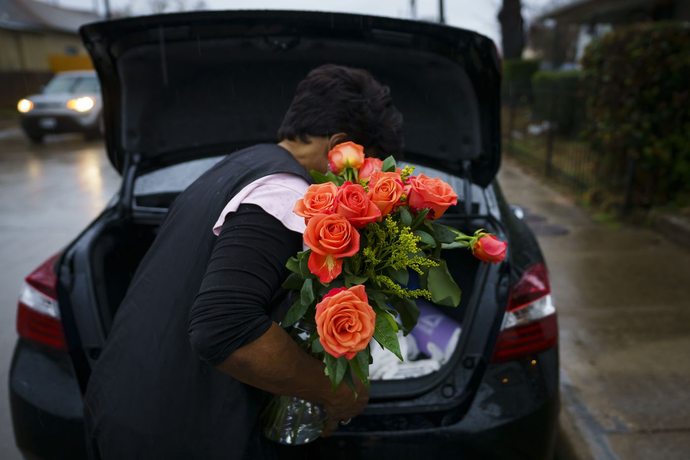 Earnestine Tarrant takes a vase of flowers that were given to her by a client in recognition of her retirement to her car after her final client.