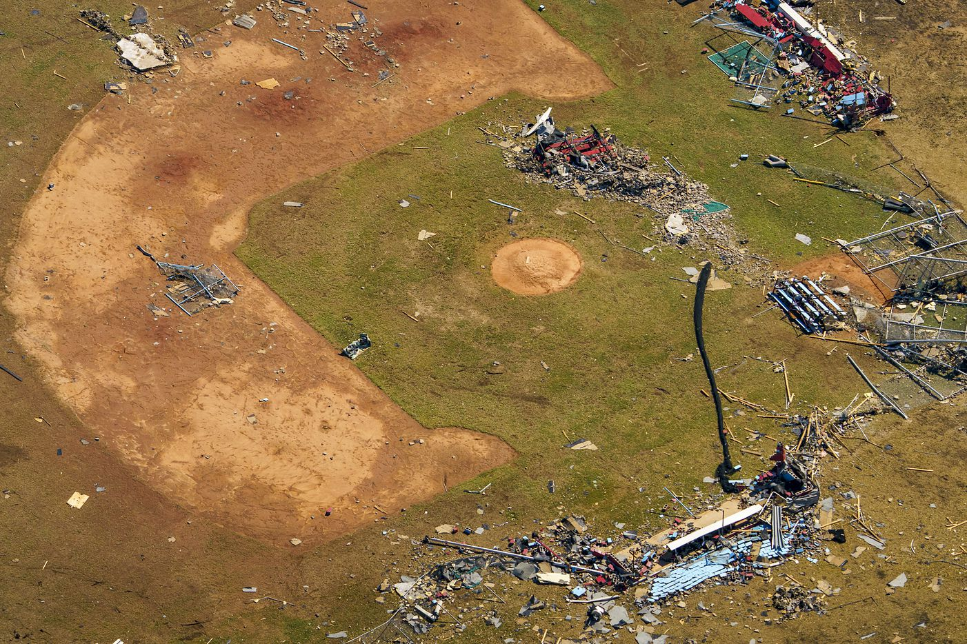 Debris from tornado damage is strewn across a baseball field at Thomas Jefferson High School on Monday, Oct. 21, 2019, in Dallas.