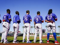 FILE - Rangers outfielder Henry Ramos (67), infielder Isiah Kiner-Falefa (9), outfielder Eli White (76), infielder Osleivis Basabe (1) and outfielder Yanio Perez (21) stand for the national anthem before a spring training game against the Cincinnati Reds at Goodyear Ballpark  on Monday, Feb. 24, 2020, in Goodyear, Ariz.
