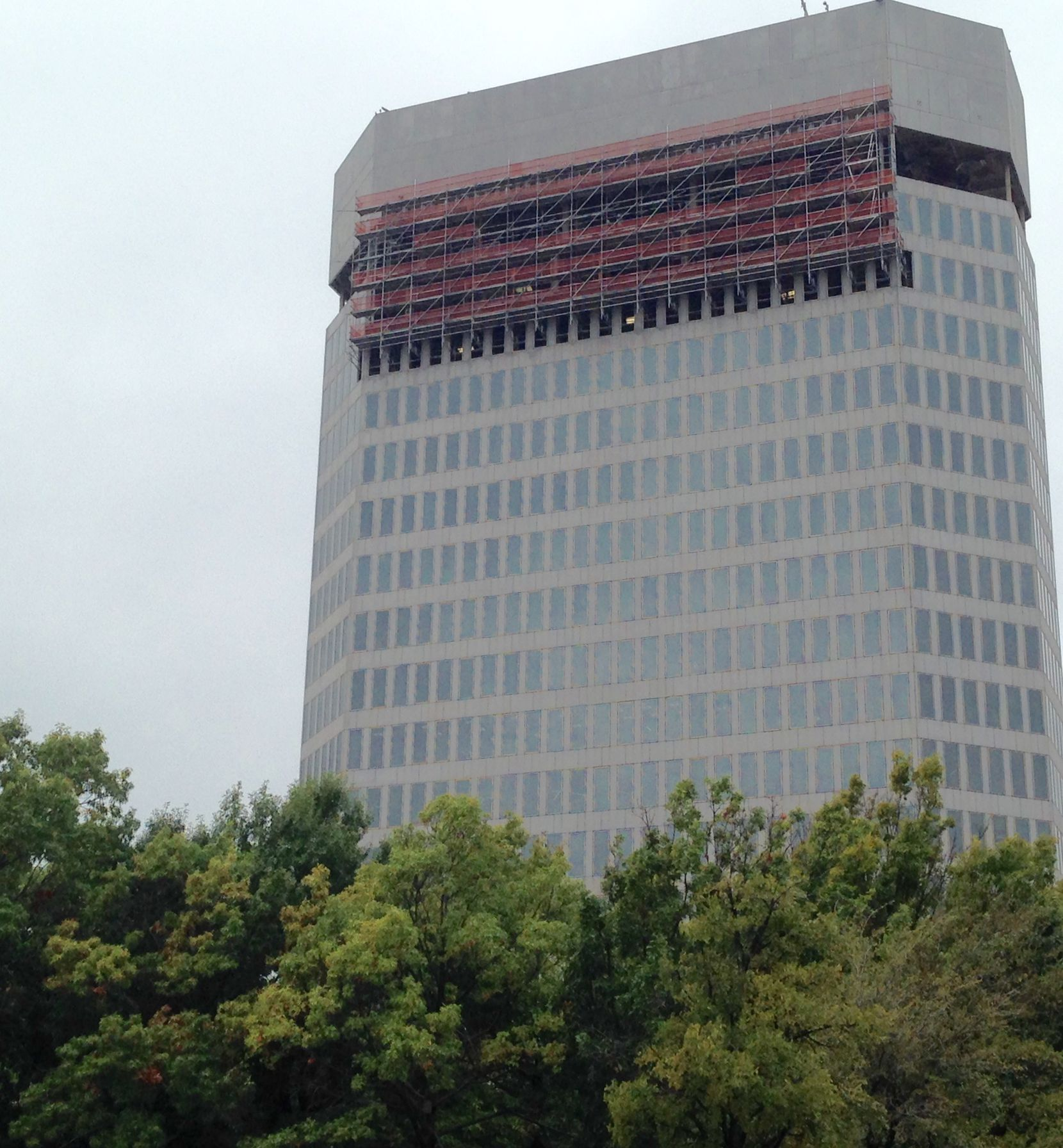 Work crews are still removing the exterior on the upper floors of the 400 Record building downtown.