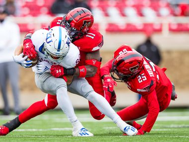 LUBBOCK, TEXAS - DECEMBER 05: Safety Eric Monroe #11 of the Texas Tech Red Raiders tackles receiver Luke Grimm #80 of the Kansas Jayhawks during the second half of the college football game at Jones AT&T Stadium on December 05, 2020 in Lubbock, Texas.