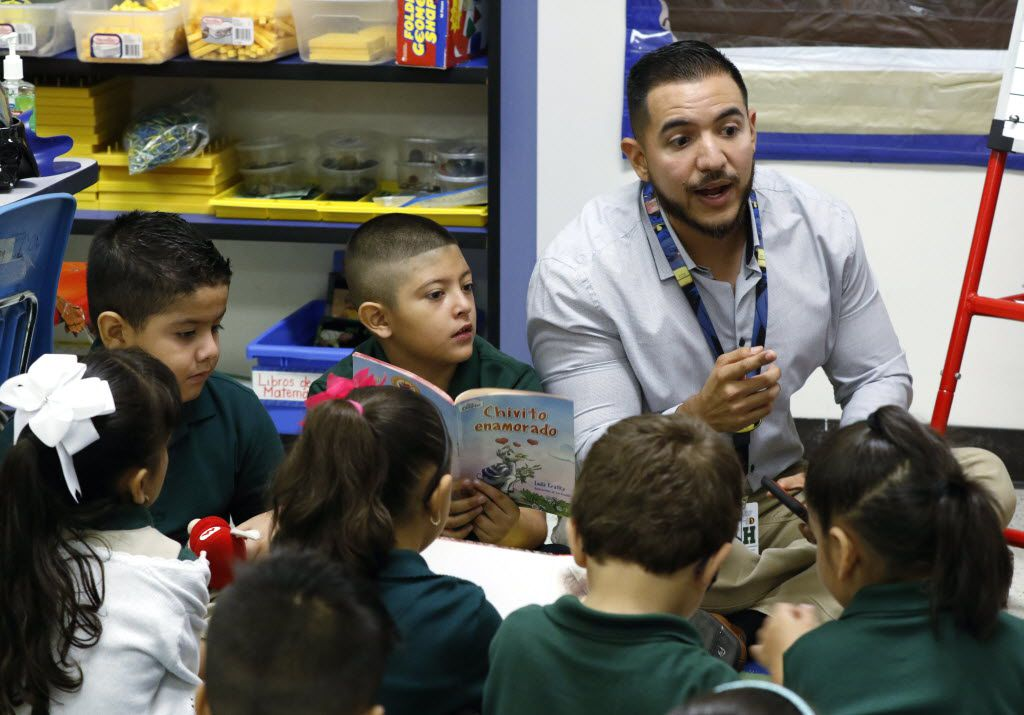 First graders Fernando Gonzalez, 6, left, and Daniel Mendez, 6, center, take part in a reading exercise with bilingual teacher Abraham Robledo at James S. Hogg Elementary School in Dallas, Wednesday, August 24, 2016.
