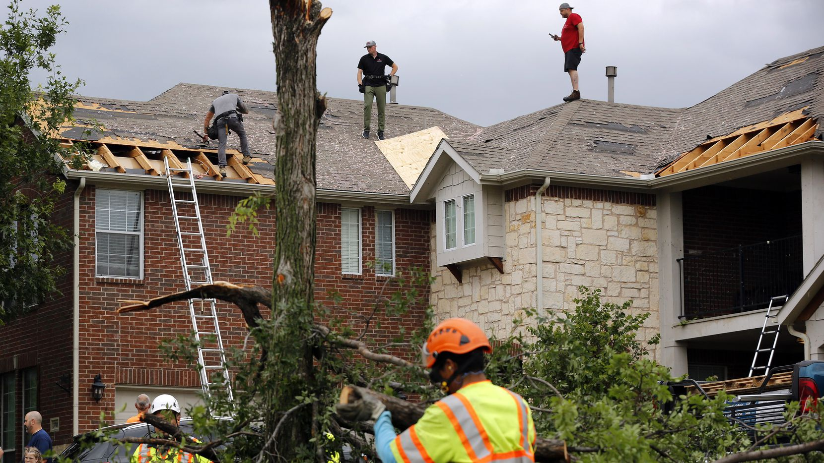 It was a hub of activity on Oliver Drive in North Fort Worth as crews cover damaged rooftops and disposed of splintered trees, Wednesday, May 29, 2019.