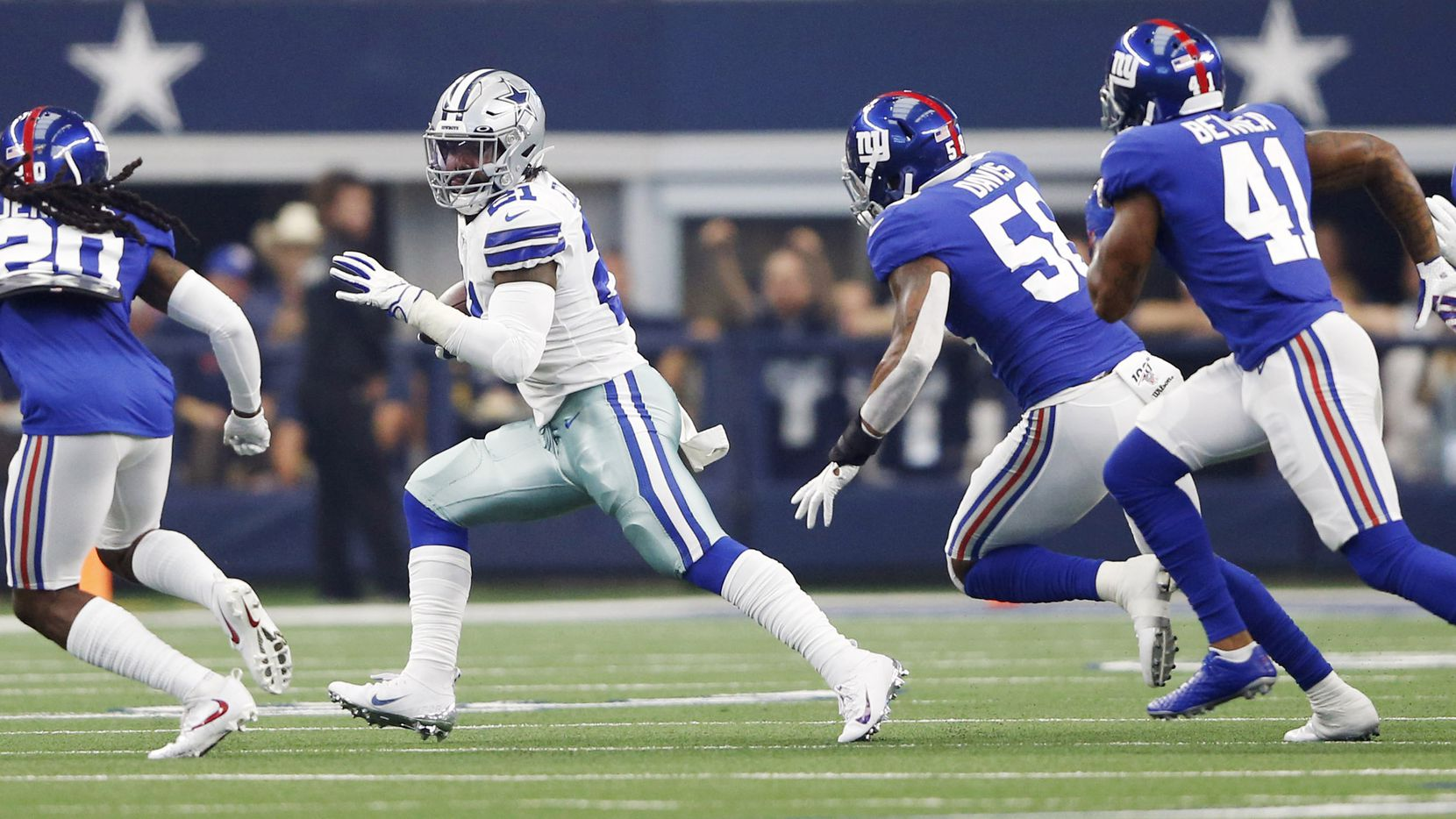 Dallas Cowboys running back Ezekiel Elliott (21) rushes up the field as New York Giants cornerback Janoris Jenkins (20) and New York Giants linebacker Tae Davis (58) chase him during the first half of play in the home opener between the Dallas Cowboys and New York Giants at AT&T Stadium in Arlington, Texas, on Sunday, September 8, 2019.