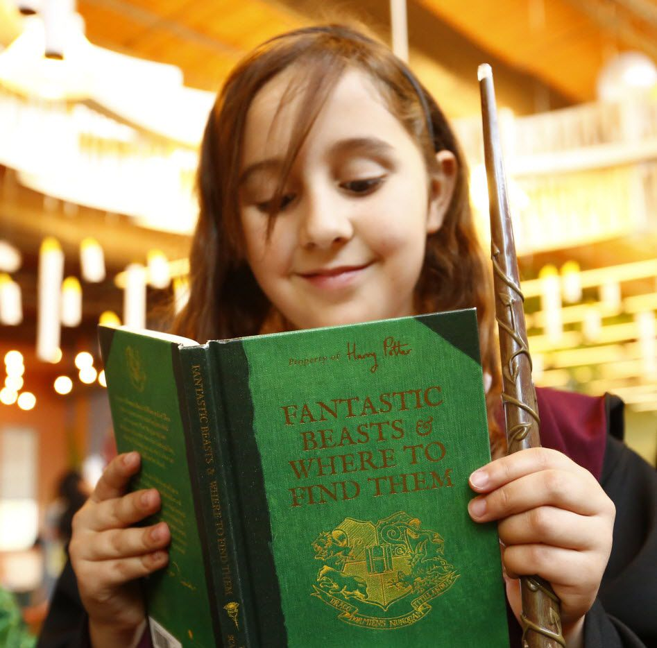 Alexa Houle, 9, reads during a Harry Potter costume contest at the Rita & Truett Smith Public Library in Wylie.