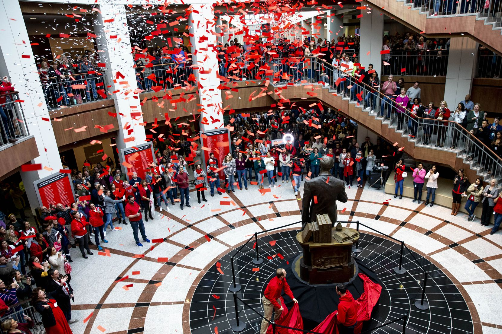 Employees pop confetti as Johnathan Dagerath, left, and Michael Fountas, right, unveil the James Cash Penney statue in its new spot in the north atrium of the J.C. Penney headquarters in Plano on March 1, 2019.