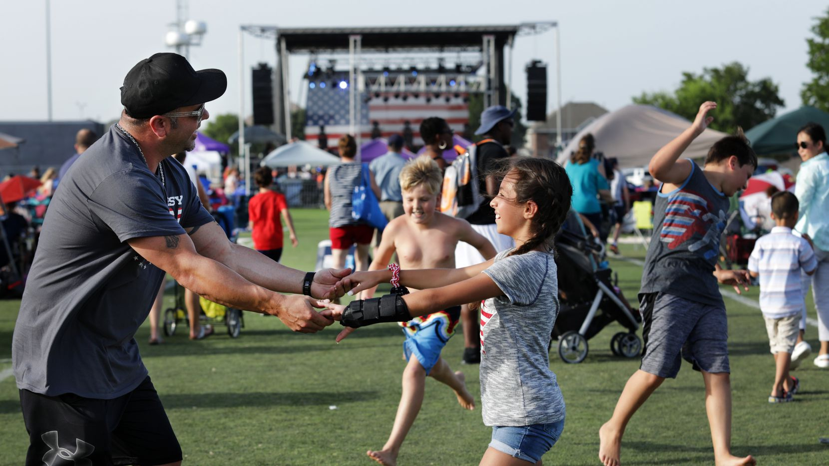 Ted Paulmeno, left, and 11-year-old Adriana Paulmeno dance to the music during the Allen USA Celebration at Celebration Park in Allen, TX, on June 30, 2018.