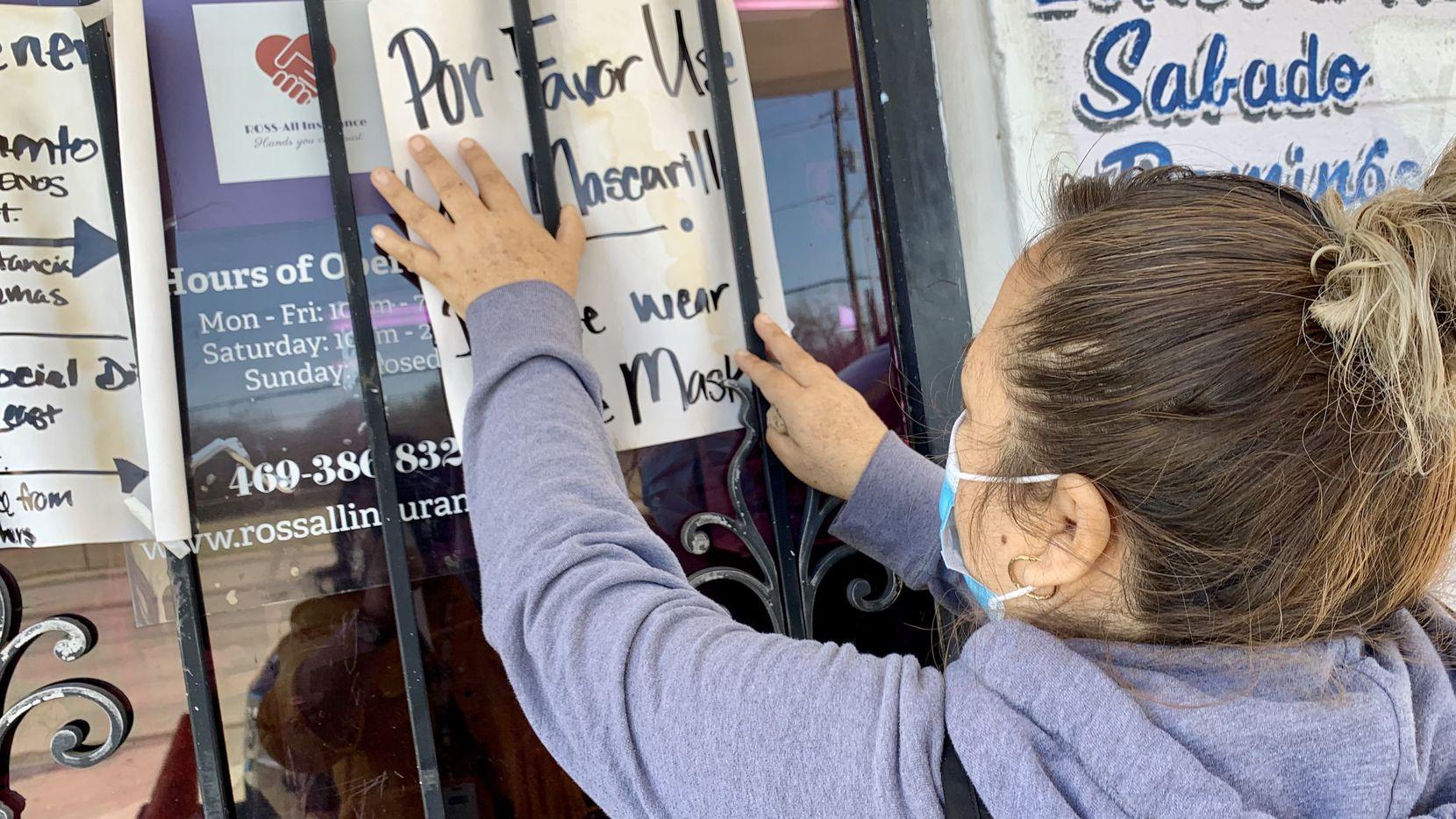 María Elena Chávez, 42, acomoda un letrero afuera de su estética, en Crocker Hill Ave., en Oak Cliff, para pedir a sus clientes que usen un cubrebocas si van a entrar a su negocio.