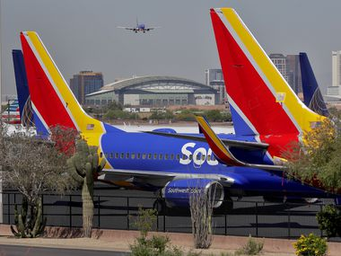 A Southwest airlines jet making its final approach backdrops stored at Southwest jets at Sky Harbor International Airport Tuesday, April 28, 2020, in Phoenix. Southwest Airlines posted its first quarterly loss in almost a decade and sees no improvement in air travel through June due to the COVID-19 coronavirus outbreak. (AP Photo/Matt York)