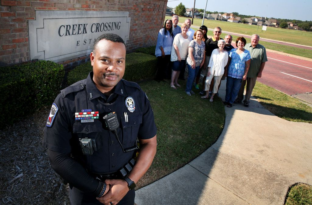 Mesquite crime prevention officer Torrey Rhone poses for a photograph with members of the Creek Crossing crime watch at the entrance to the neighborhood in Mesquite, Texas on Saturday, Sept. 23, 2017. (Rose Baca/The Dallas Morning News)