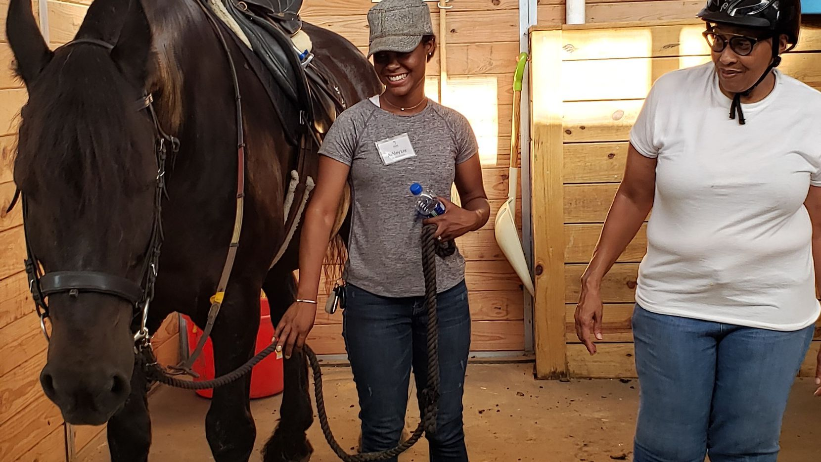 Army veteran Charmayne Baycock (right) and Hooves for Horses volunteer Ashley Lay finish grooming Hampton before taking him to the training ring for Baylock to ride him.