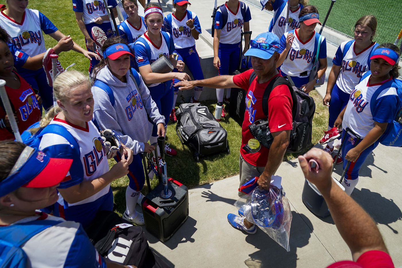Texas Glory 18U players gather around coach Kevin Shelton after a victory against the American Freedom Gold Coleman 18U during a Triple Crown Texas State Tournament game at Spirit Park on Monday, June 15, 2020, in Allen, Texas. (Smiley N. Pool/The Dallas Morning News)