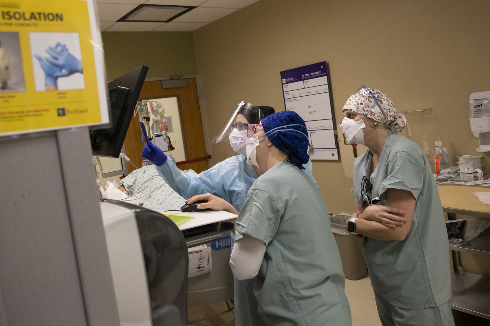 From left: Nurses Kelsey O'Meara, Noelle Hackfeld and Joanna Pless review an intubated COVID-19 patient's oxygen levels in the Tactical Care Unit at Parkland Memorial Hospital.