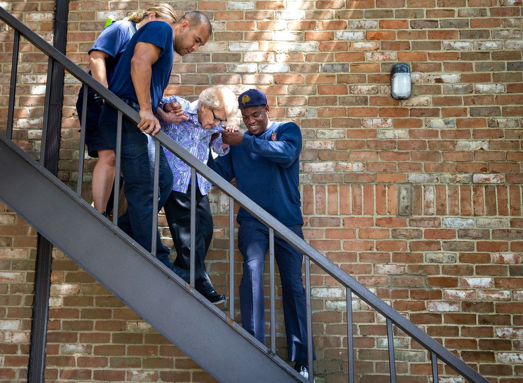 """Dallas firefighters help Agnes """"Mickey"""" Santillo, 99, down the stairs at her condominium for a trip to her favorite restaurant, El Fenix, with friends. Santillo has been in hospice care since May."""
