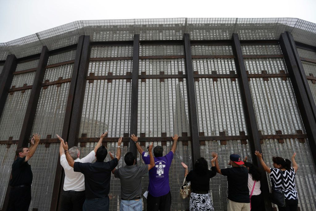In this July 14, 2013, photo, pastors and others raise their arms on the San Diego side of a border fence during a cross-border Sunday religious service with others on the Tijuana, Mexico, side of the fence.