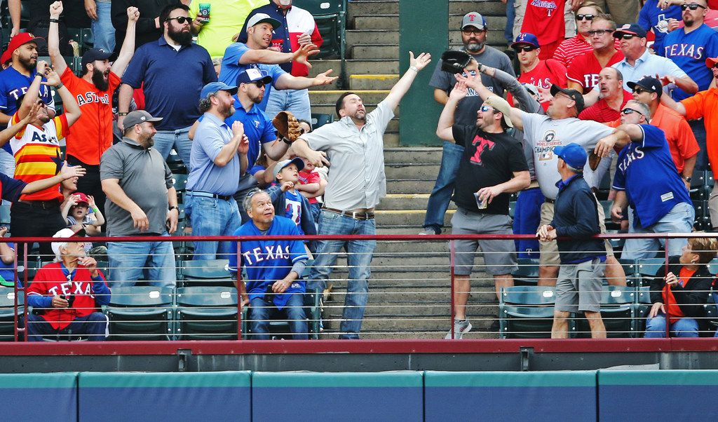FILE - Fans in right field leap to catch George Springer's first-inning home run during a Rangers-Astros game at Globe Life Park in Arlington on Thursday, March 29, 2018.  (Louis DeLuca/The Dallas Morning News)