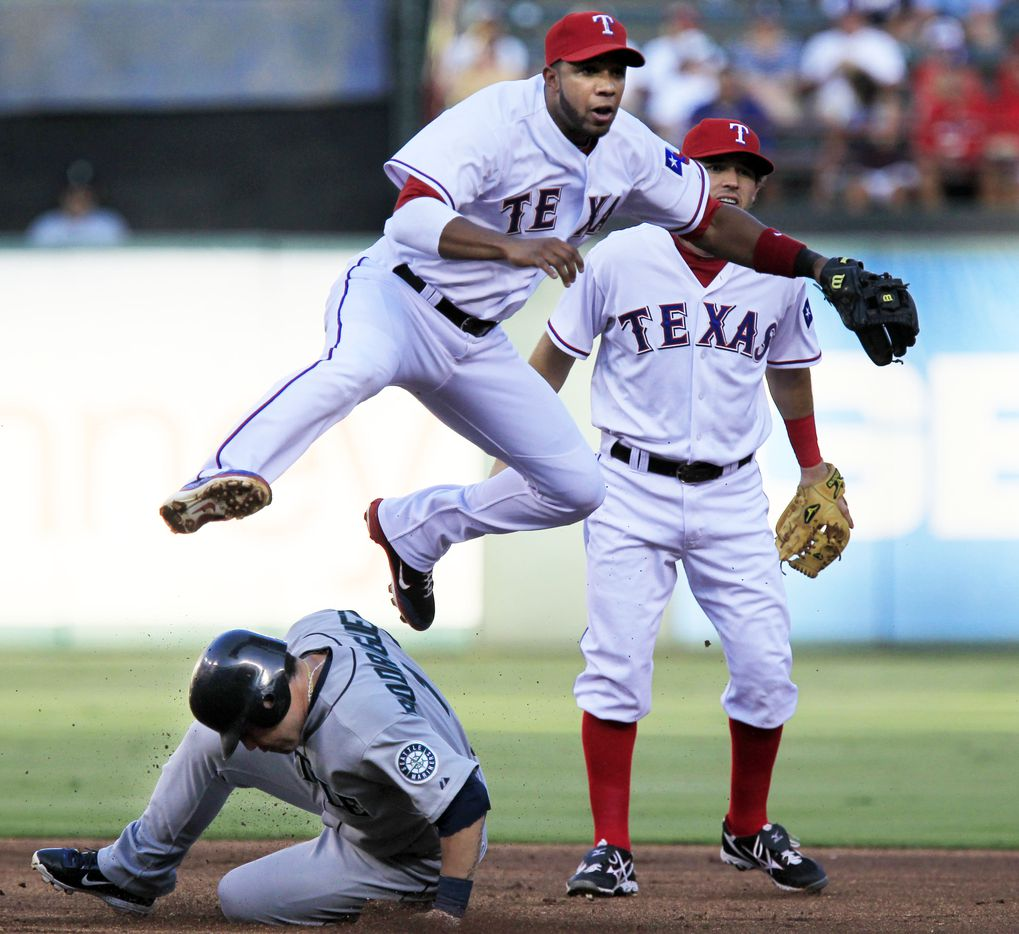 Texas Rangers shortstop Elvis Andrus (1) goes high to avoid sliding Seattle Mariners shortstop Luis Rodriguez (1) to get the double play during first inning MLB baseball action between the Texas Rangers and the Seattle Mariners at Rangers Ballpark in Arlington on August 10, 2011. Texas Rangers second baseman Ian Kinsler (5) watches. The Rangers lost 4-3.  (John F. Rhodes / The Dallas Morning News)