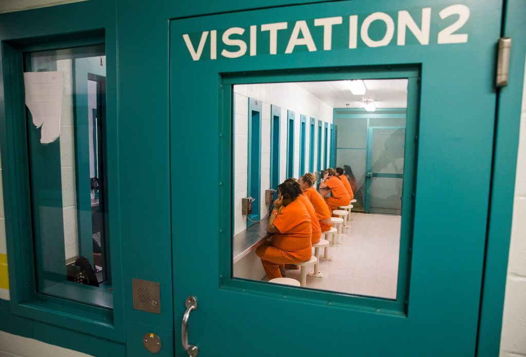 Female inmates talk to visitors through glass in October at Burnet County Jail. The jail houses women from several other counties, whose family may travel two hours or more for weekly visits.