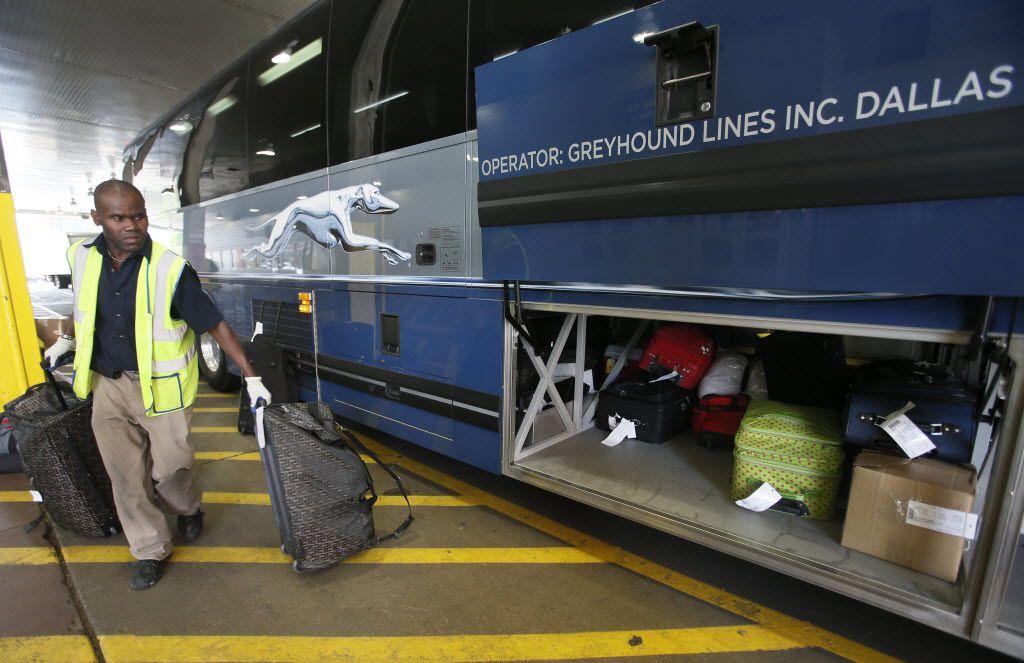 Myron Thomas loads the luggage onto a  Greyhound bus in downtown Dallas.