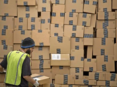 An employee loads a truck at an Amazon.com fulfillment center in Phoenix. In Texas, where Amazon began collecting sales taxes in June 2012, the online retailer and other e-commerce firms are seeing a surge in sales because of the coronavirus pandemic, Comptroller Glenn Hegar says.