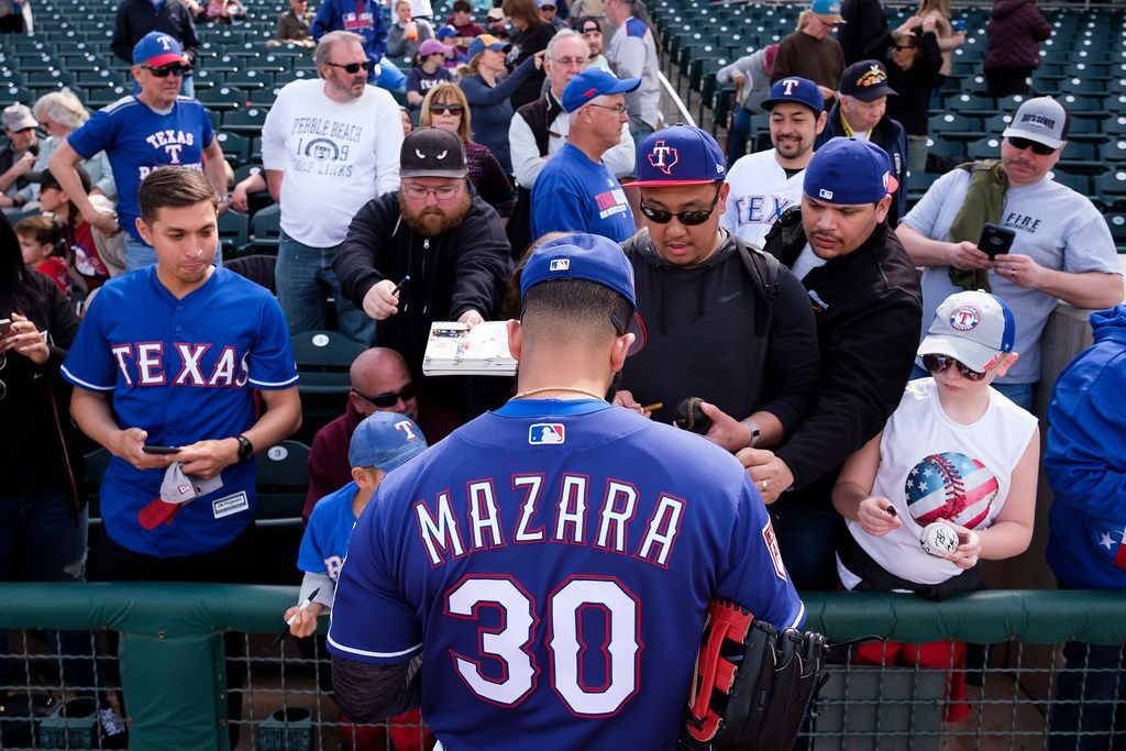Texas Rangers outfielder Nomar Mazara signs autographs before a spring training baseball game against the Milwaukee Brewers at Surprise Stadium on Sunday, Feb. 24, 2019, in Surprise, Ariz.. (Smiley N. Pool/The Dallas Morning News)