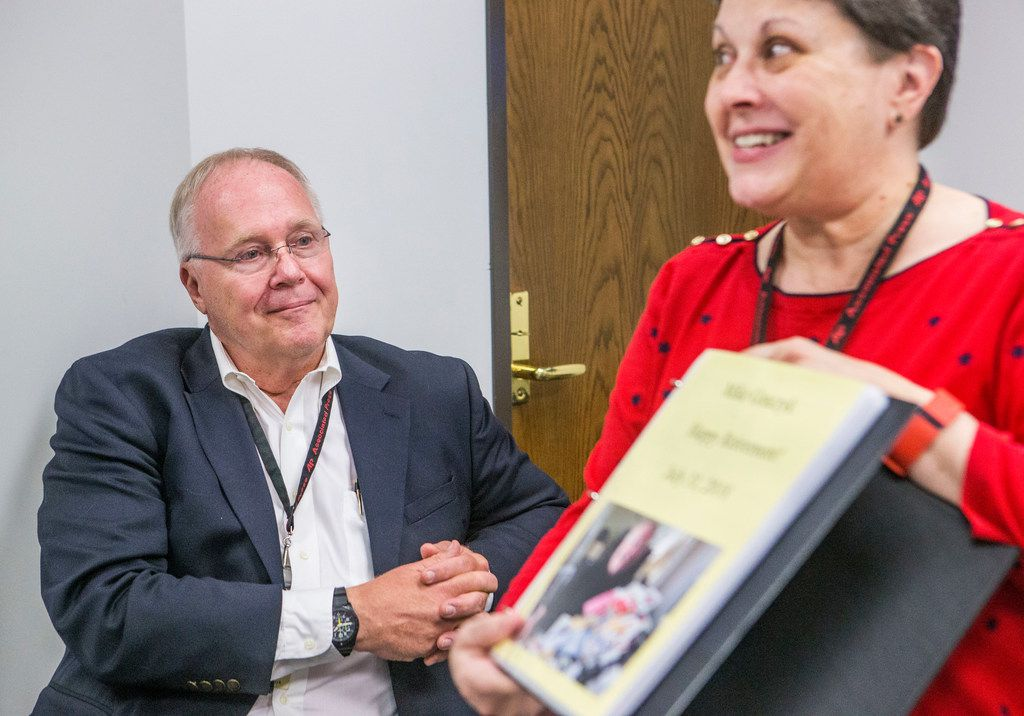 Michael Graczyk, a journalist for The Associated Press, looks at a book of notes written by his colleagues, held by Diana Heidgerd, during a retirement celebration at the AP Dallas News Bureau in Dallas on July 31, 2018. Over his career, Graczyk has witnessed and documented hundreds of executions in Texas.
