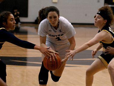 Denton Guyer's Evie Goetz drives between McKinney's Trinity White, left, and Emily Barnhill in the first half of a girls high school basketball game between McKinney and Denton Guyer, Tuesday, Dec. 15, 2020, in Denton, Texas.