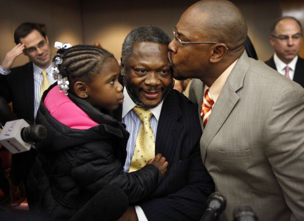 While holding his 4-year-old granddaughter Caribbean Hill for the first time, Rickey Wyatt, 56, of Dallas receives a kiss from his nephew Robert Smith of DeSoto after he was set free.