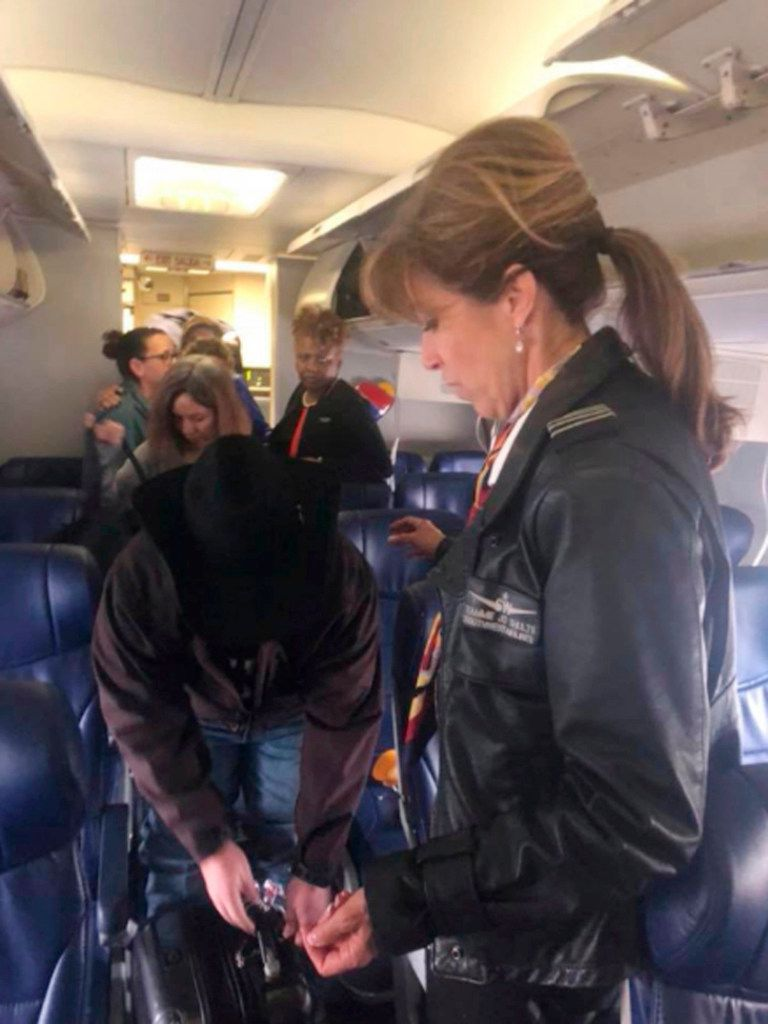 This photo provided by Diana McBride Self shows Flight 1380 pilot Tammie Jo Shults, right, interacting with passengers after safely landing the Southwest Airlines plane on Tuesday, April 17, 2018. Passengers praised Shults for her professionalism during the emergency. She walked through the aisle and talked with passengers to make sure they were OK afterward.