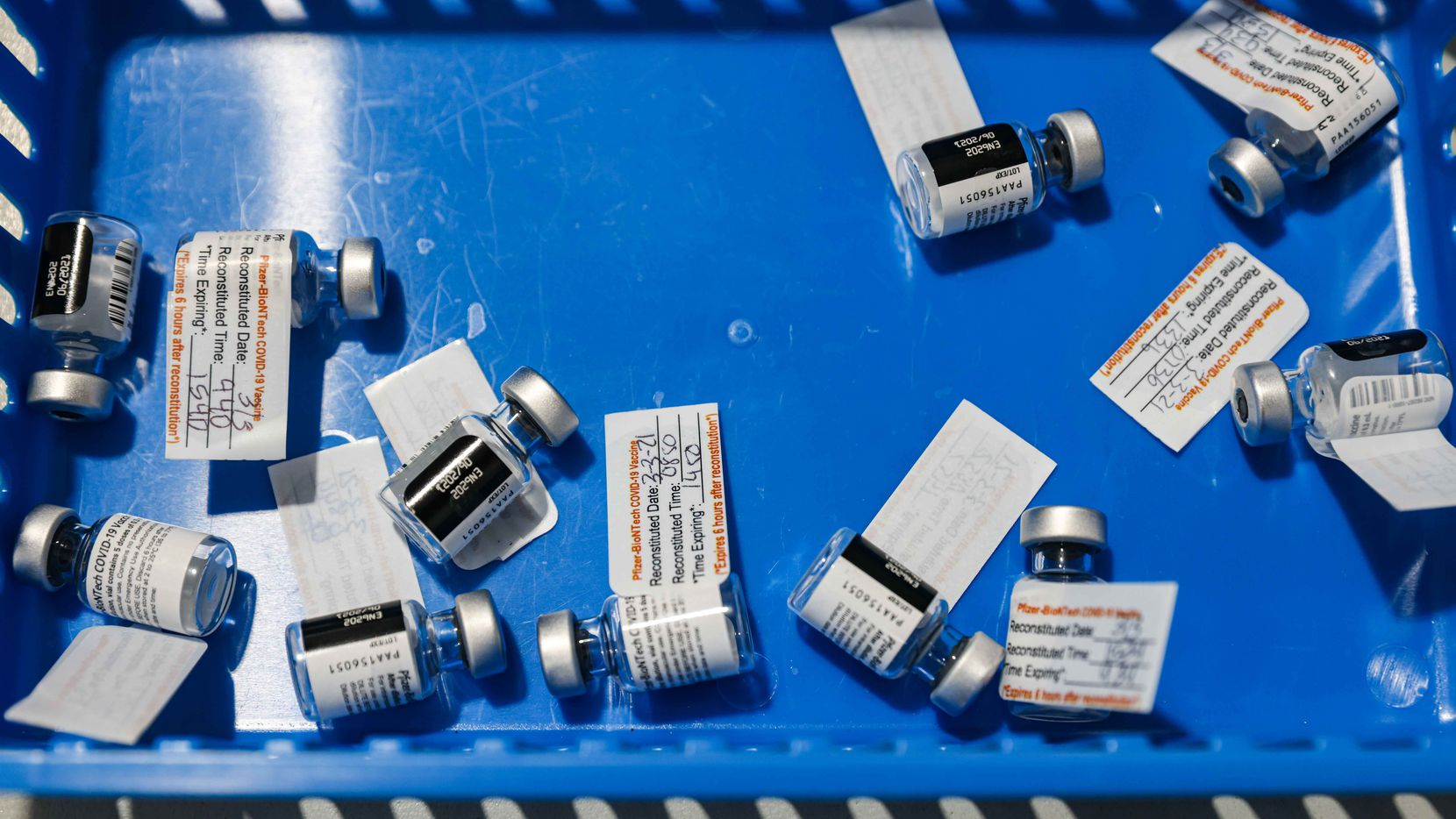 Used Pfizer-BioNTech COVID-19 vaccine vials rest in a blue tray at Ellis Davis Fieldhouse, a Parkland Hospital testing and vaccine location, in Dallas on Wednesday, March 3, 2021.