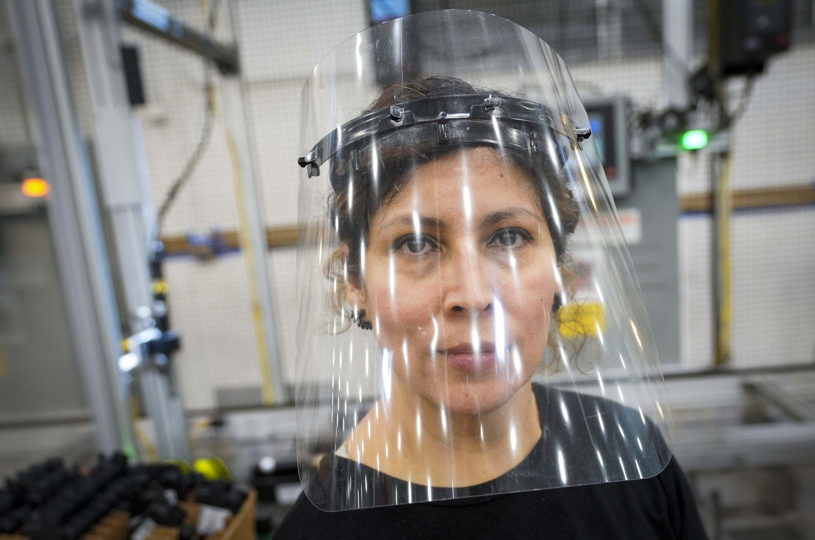 Face coverings are not required for everyone at Flex-N-Gate, but about half the workers wear masks or face shields, including Blanca Ortega, seen on the production line at the Grand Prairie factory.
