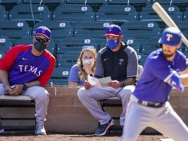 Texas Rangers manager Chris Woodward (right) and bench coach Don Wakamatsu watch designated hitter David Dahl bat during the fourth inning of a spring training game against the Arizona Diamondbacks at Salt River Fields at Talking Stick on Saturday, March 6, 2021, in Scottsdale, Ariz.