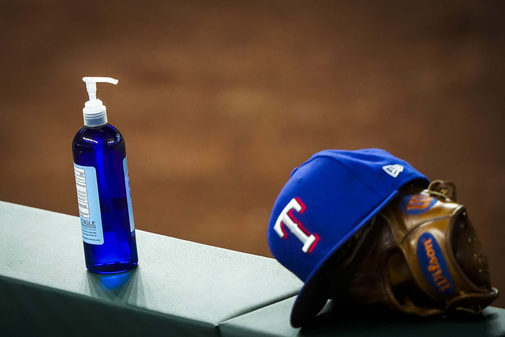 A bottle of hand sanitizer rests on the dugout railing during a Texas Rangers Summer Camp  intrasquad game at Globe Life Field on Saturday, July 18, 2020.