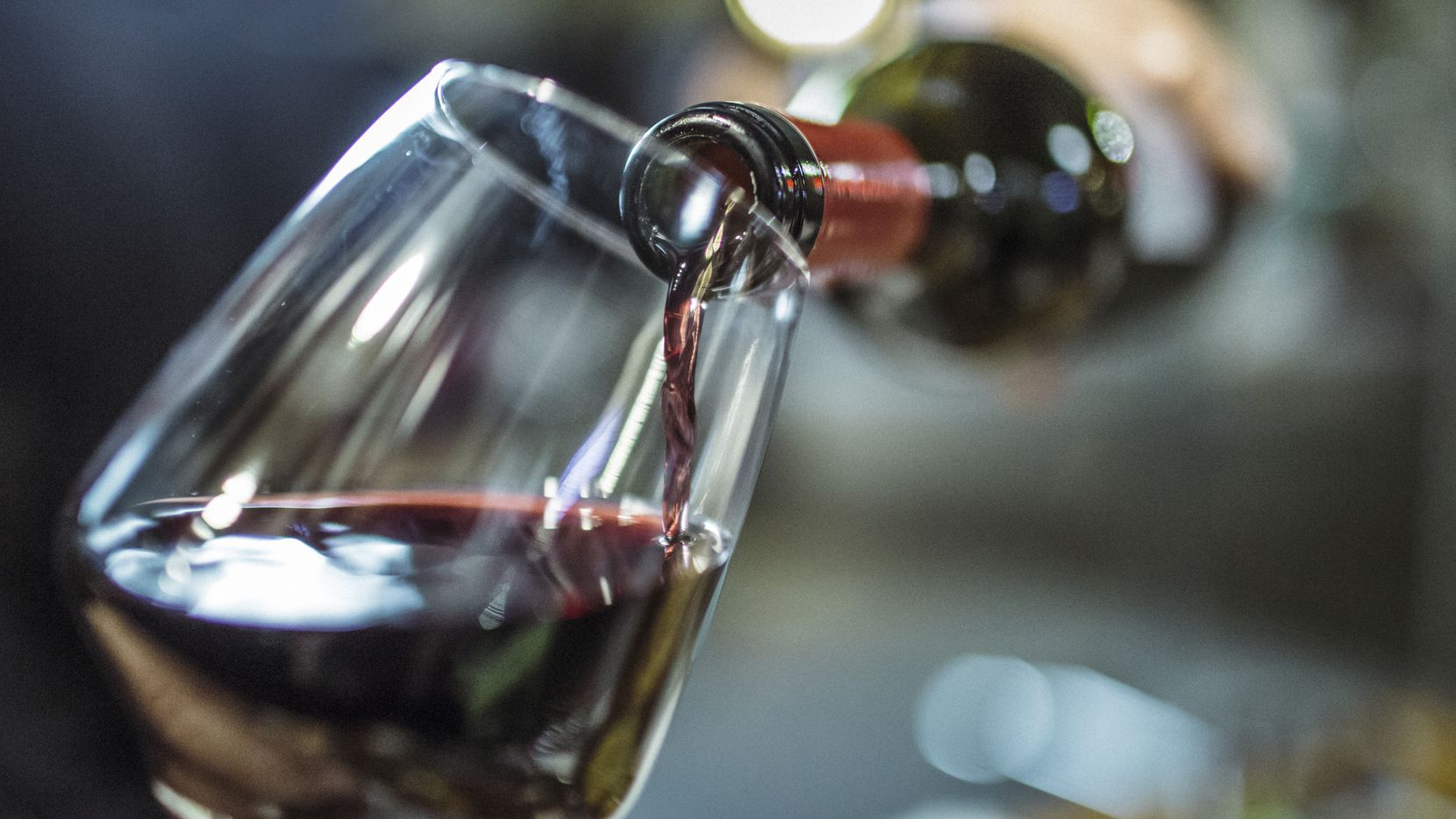 Red wine is poured into a wine glass.