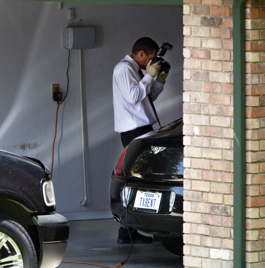 A law enforcement agent photographs a Bentley owned by John Wiley Price that was parked in the garage at the home of Dapheny Fain, top assistant to John Wiley Price, in DeSoto, Texas in June 2011, as FBI agents began searching the offices and home of longtime Dallas County commissioner John Wiley Price and those of several of his associates.