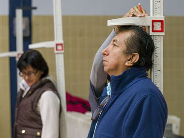Participants get their height and weight checked this month during a health fair sponsored by Blue Cross and Blue Shield of Texas. Over 5 million are uninsured in Texas, far more than any other state.